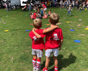 Two boys with didi rugby shirts on watch a game