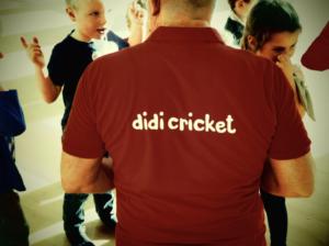 Children talk to a man wearing a didi cricket tee-shirt