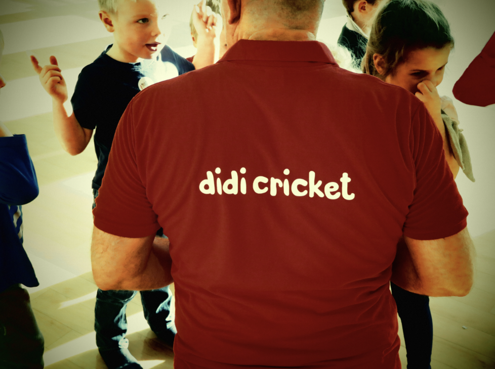 Children talk to a man wearing a didi cricket tee-shirt
