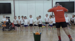 didi cricket coach Keith Smith has fun with a class of children in a sports hall