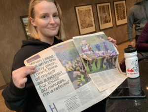 didi rugby Birstall coach Jenny Burrows holds up a newspaper featuring a story about herself