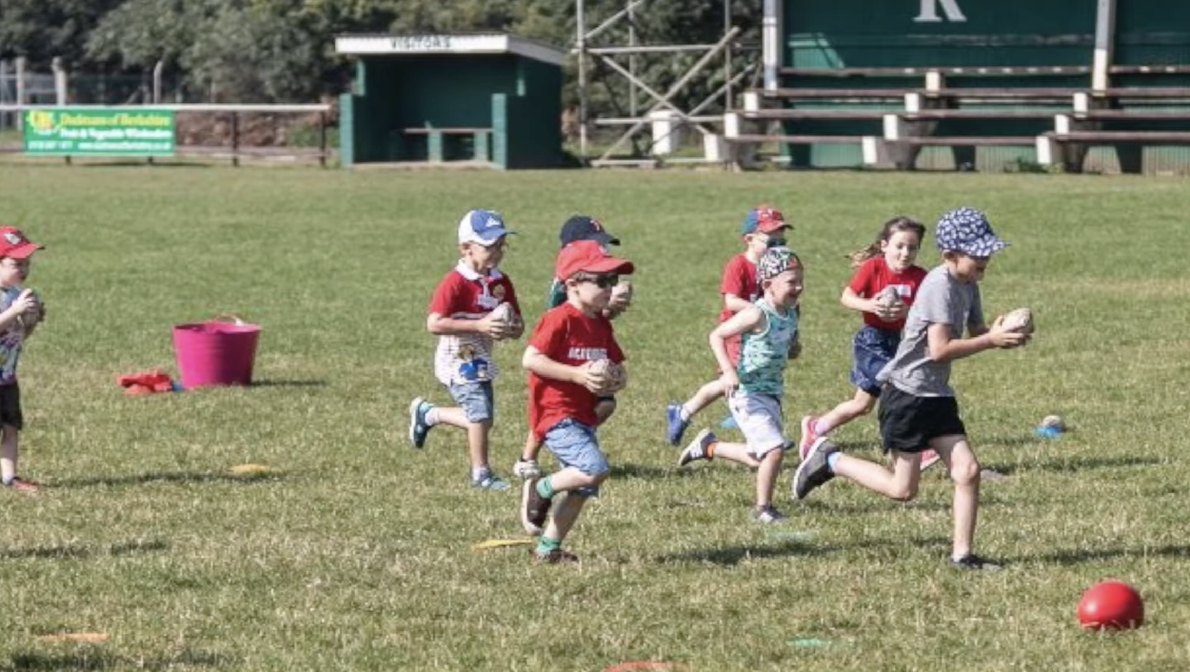 Children run around with balls in their hands at Reading Rugby Club's didi rugby session