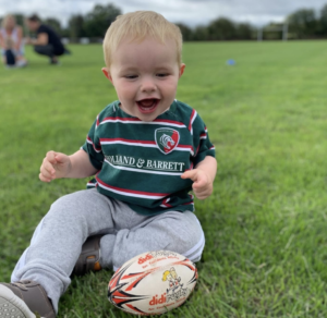 A young boy in a Leicester Tigers top plays with a didi rugby ball ahead of the launch of classes at Oadby Wyggestonian RFC