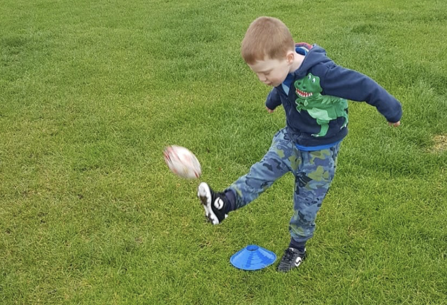 Zachary kicks the ball at a didi rugby session at Birstall Rugby Club