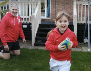 A small girl running with a rugby ball in her hand, smiling