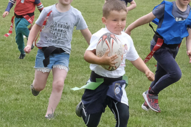 A boy runs away from chasers with a didi rugby Cornwall ball in his hand